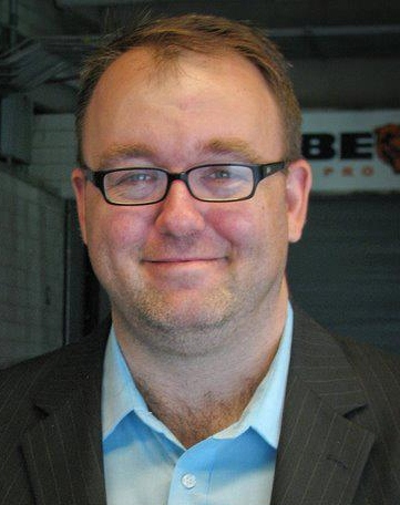 man wearing glasses, light blue dress shirt and dark blue jacket