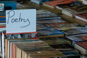 books on a sales table with a sign with the words poetry