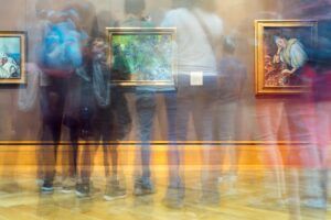 blurry image of people standing in a gallery looking at framed paintings.